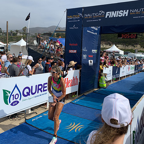 A Woman runner who cross the Malibu Finish line featuring QURE Water