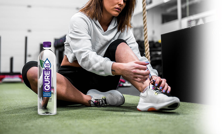 A woman with QURE 10pH Alkaline Water shoe lacing her shoes while preparing for a workout